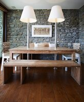 Rustic wooden dining table with integrated modern standard lamps in dining room with stone walls