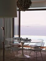 Dining area with classic, white plastic table and wire frame chairs in front of terrace window with sea view