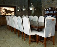 Chairs with white leather upholstery at long table and pendant lamps with stainless steel lampshade in rustic setting