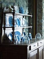 White and blue crockery displayed in top section of antique dresser