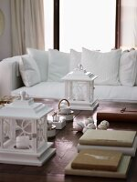 White lanterns on wooden coffee table in front of white sofa with scatter cushions