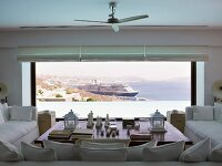 Sofa set on three sides of coffee table in front of panoramic window with view of cruise ship on sea