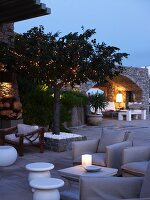 Twilight Mediterranean terrace with armchairs upholstered in grey and various side tables