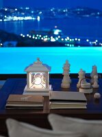 Lantern and chess pieces on coffee table in front of panoramic window with view of illuminated pool and twilit seashore