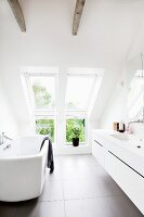 Modern bathtub opposite washstand with integrated sink in designer bathroom with dormer window