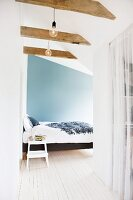 Attic bedroom with bed against blue wall and pale wooden floor