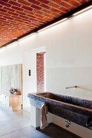 tellerstapel und besteck auf beton arbeitsplatte mit integrierter sp le vor holzverkleideter. Black Bedroom Furniture Sets. Home Design Ideas