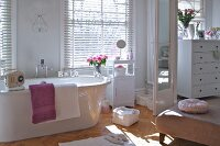 Elegant white bathroom with blinds at windows