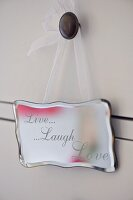 Silver sign with motto 'Live Laugh Love' hanging on drawer knob