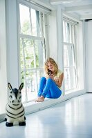 Teenage girl sitting on window sill in white interior; toy animal in foreground