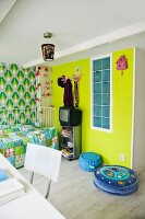 Original child's bedroom with patchwork blanket and retro wallpaper next to yellow-painted wall