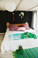 Unusual colour scheme in bedroom; pink scatter cushions on bed against black wall combined with rag rug in shades of green