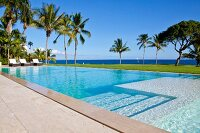 View past steps leading down into elongated pool to palm trees and Caribbean sea