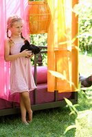 Summer idyll - little girl holding black cockerel in front of couch in Oriental colours