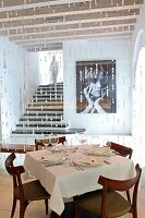 Set table in front of bead curtain in hotel restaurant and view of photo on wall next to recessed staircase