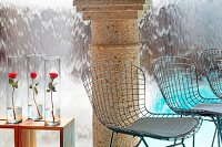 Wire chairs and roses in glass vases on side tables in front of stone column and waterfall sheeting into pool