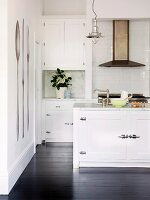 White fitted kitchen with retro elements and black wooden floor