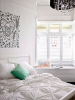 White double bed with green scatter cushion below romantic print on wall; comfortable window seat in window niche