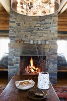 Coffee table in front of open fireplace in stone chimney breast