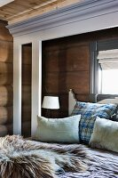 Fur blanket and scatter cushions on double bed in corner of log cabin