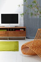 Modern chair made from bent wooden slats in front of green rug on white tiled floor and flat-screen TV on lowboard