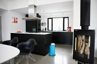 Modern interior in black and white - dining area with classic chairs in front of free-standing kitchen island and log burner