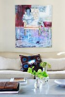 Flowers on coffee table in front of modern sofa and painting on pale grey wall