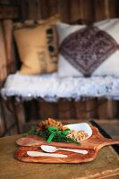Chanterelles, walnuts, herbs and wooden spoons on wooden board; cushions on wire bench in blurred background
