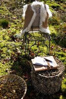 Fur waistcoat hanging on wire chair behind open notebook and pen on small, artistic side table in sunny woodland clearing