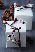 Gift boxes decorated with garlands of red and white berries