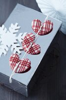 Wrapped Christmas present decorated with red and white checked fabric hearts and wooden snowflake