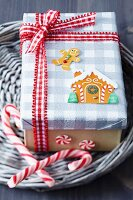 Gift box festively decorated with gingerbread stickers, red and white checked ribbon and candy canes