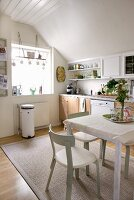 Bright, white kitchen-dining room with wooden base units and classic Scandinavian chairs