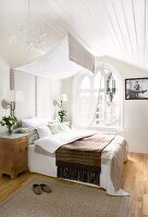 Bed with upholstered headboard and canopy in attic room with arched window and white wooden ceiling