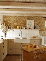 Storage jars of groceries on kitchen island in front of counter with tiled splashback on stone wall in rustic setting