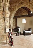 Armchairs with black leather upholstery on terracotta tiles in spacious, restored stone house