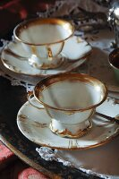 Two antique white china teacups with gold trim
