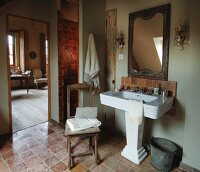 Vintage-style bathroom with old terracotta tiles and crystal sconce lamps above French pedestal washbasin