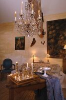 Traditional interior - lit candles in chandelier above table and full champagne glasses on tray