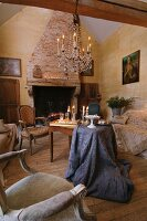 Chandelier with lit candles in rustic living room with traditional seating and brocade tablecloth draped on simple wooden table