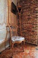 Upholstered chair with Rococo-style gilt wooden frame and processional staff leaning on brick wall in corner of room