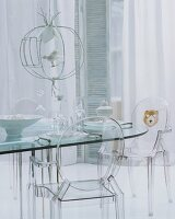 Transparent modern interior - clear plastic chairs at glass table and airy curtain