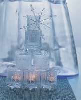 Pyramid of tealight holders made of crystal-style glass and decorative snowflake ornament in front of glass vase