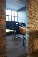 Stone-clad partition wall of loft studio apartment with view of desk and office chair beyond