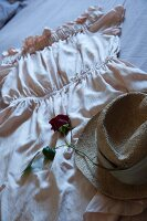 Rose and straw hat arranged on dress spread out on bed