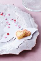 Heart-shaped biscuits and sugar hearts on paper butterfly