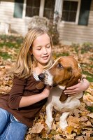 Girl hugging dog outdoors