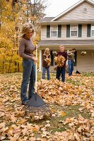 Family cleaning up autumn leaves