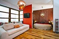 Comfortable sofa below window next to TV on partition screening sleeping area in open-plan, modern interior