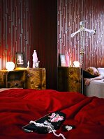 Bead necklace and evening bag on red bedspread next to small, antique bedside cabinet and mirrored wardrobe